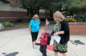 Principal Twibell helps a new Puma student on the 1st Day of Kindergarten (8/24/17)